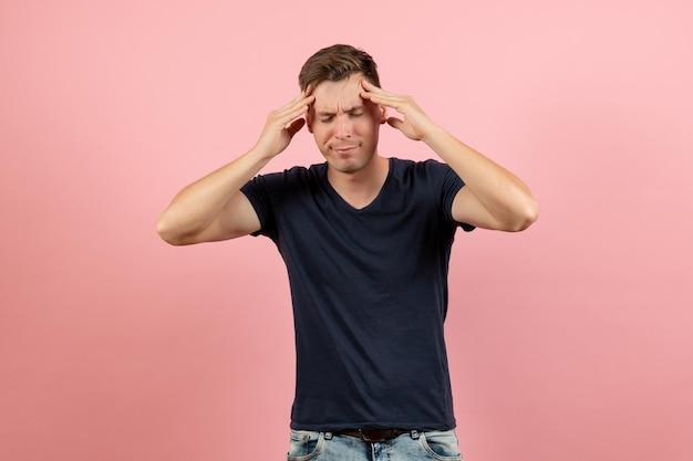Vue de face jeune homme en chemise bleu foncé souffrant de maux de tête sur fond rose