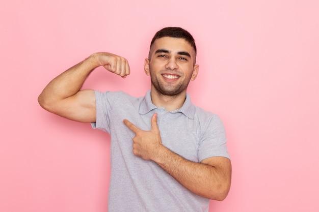 Vue De Face Jeune Homme En Chemise Grise Posant Et Souriant Avec Flex Sur Rose Photo gratuit
