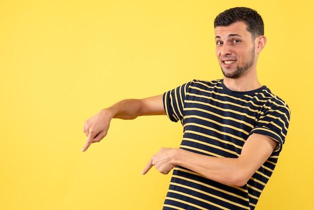 Vue de face jeune homme en chemise rayée noir et blanc pointant au sol sur fond isolé jaune