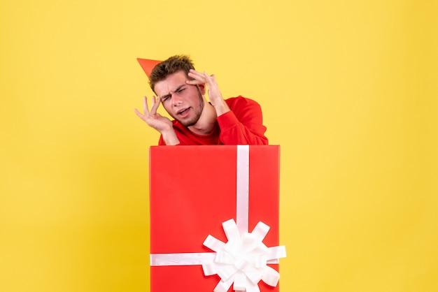 Vue de face jeune homme en chemise rouge à l'intérieur de la boîte actuelle