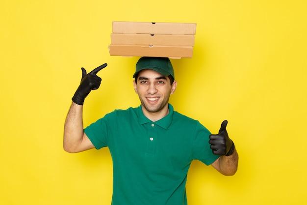 Vue de face jeune homme en chemise verte casquette verte tenant des boîtes de livraison sur sa tête souriant sur jaune