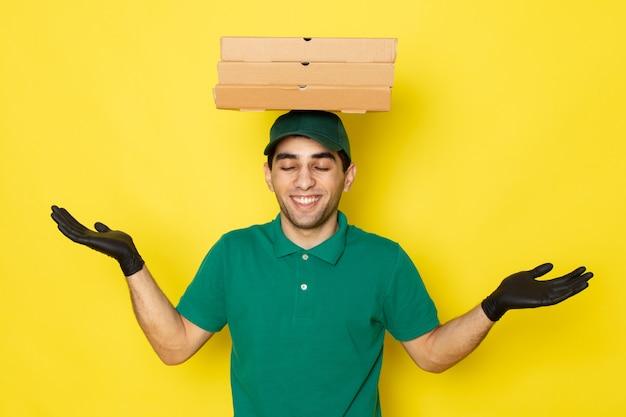 Vue de face jeune homme en chemise verte casquette verte tenant des boîtes de livraison sur sa tête avec sourire sur jaune