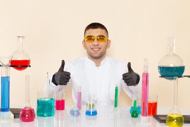 Vue de face jeune homme chimiste en costume spécial blanc assis en face de la table avec des solutions et souriant sur l'expérience scientifique de chimie de laboratoire mur crème
