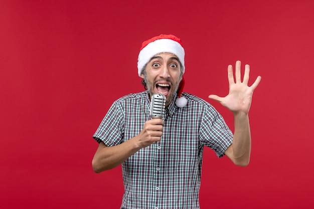 Vue de face jeune homme comptage montrant le nombre sur le mur rouge émotion vacances chanteur musique