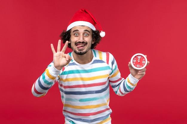 Vue de face jeune homme comptage montrant le nombre sur le mur rouge temps rouge vacances du nouvel an