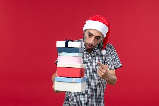 Vue de face jeune homme comptant le nombre de cadeaux sur fond rouge
