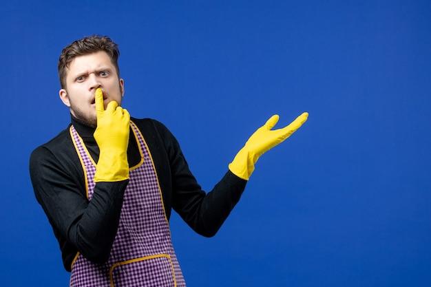 Vue de face jeune homme confus mettant le doigt sur sa bouche