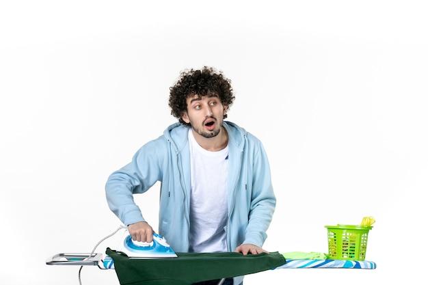 Vue de face le jeune homme continue de repasser chemise verte sur fond blanc émotion des tâches ménagères couleur fer à repasser les vêtements de nettoyage de blanchisserie