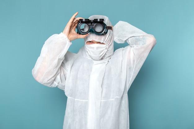 Une vue de face jeune homme en costume spécial blanc portant des lunettes de soleil spéciales sur le mur bleu homme costume couleur équipement spécial danger