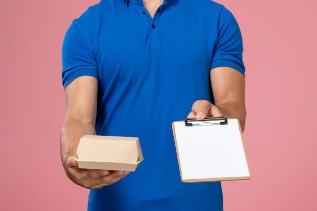 Vue de face, jeune, homme, courrier, dans, bleu, uniforme, cape, tenue, peu, livraison, paquet alimentaire, et, bloc-notes, sur, les, mur rose