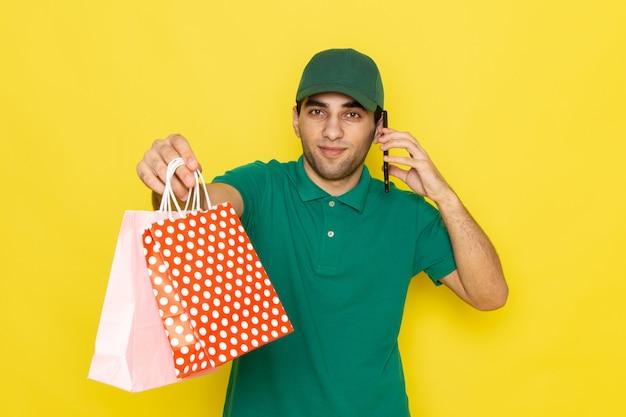 Vue de face, jeune, homme, courrier, dans, chemise verte, casquette verte, conversation téléphone