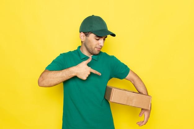 Vue de face, jeune, homme, courrier, dans, chemise verte, chapeau vert, sourire, et, tenue, boîte livraison, sur, les, fond jaune, travail, prestation service, couleur