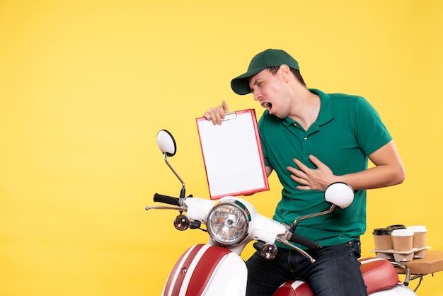 Vue de face jeune homme coursier en uniforme vert tenant une note de dossier sur jaune