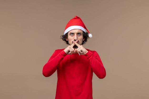 Vue de face jeune homme croisant les doigts sur un fond marron vacances émotion noël