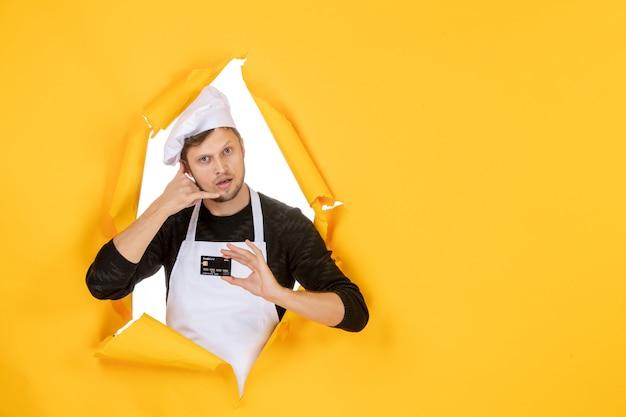 Vue de face jeune homme cuisinier en cape blanche tenant une carte bancaire noire sur le modèle de fond jaune couleur blanche cuisine emploi homme nourriture argent