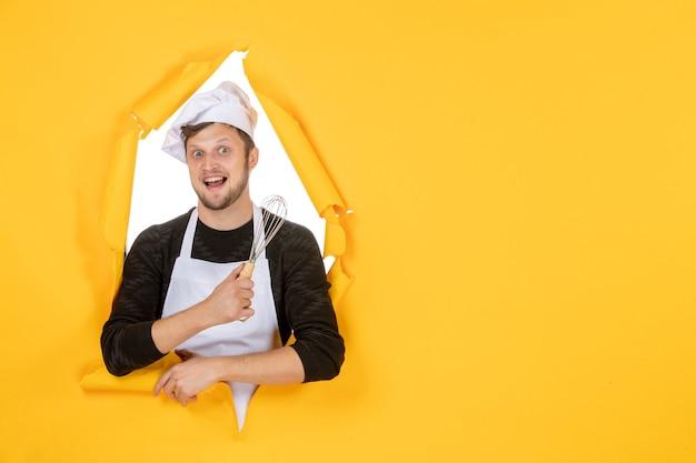 Vue de face jeune homme cuisinier en cape blanche tenant un fouet sur le fond jaune photo nourriture homme cuisine cuisine travail couleur blanc