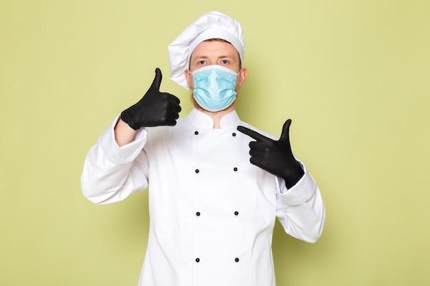 Une vue de face jeune homme cuisinier en costume de cuisinier blanc casquette blanche en gants noirs masque de protection bleu montrant un signe impressionnant