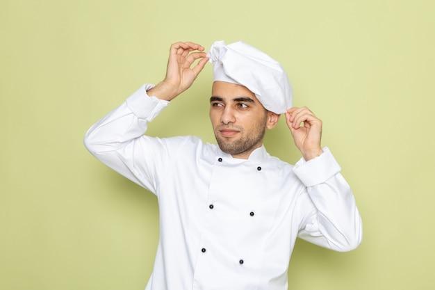 Vue de face jeune homme cuisinier en costume de cuisinier blanc fixant sa casquette sur vert