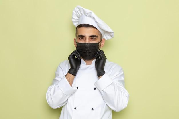 Vue de face jeune homme cuisinier en costume de cuisinier blanc portant un masque et des gants sur vert