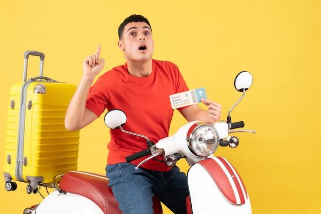 Vue de face jeune homme sur un cyclomoteur tenant un billet surprenant avec une idée ou une question