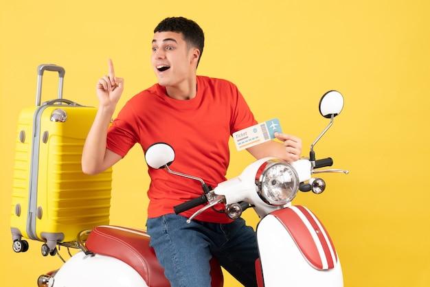 Vue de face jeune homme sur un cyclomoteur tenant un billet surprenant avec une idée