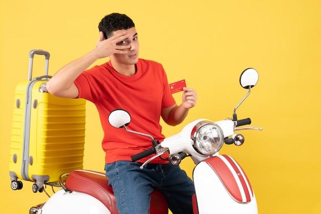 Vue de face jeune homme sur cyclomoteur tenant une carte de crédit sur fond jaune