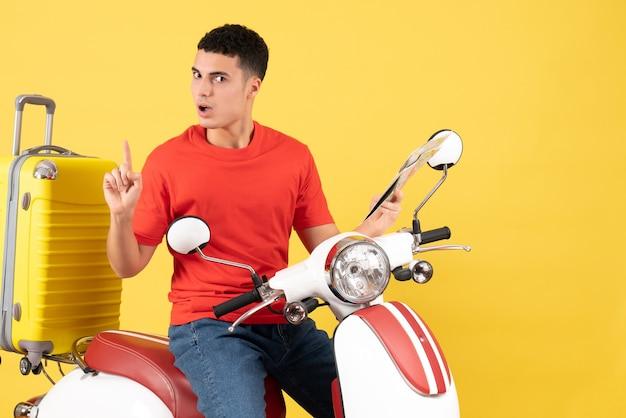 Vue de face, jeune homme, sur, cyclomoteur, tenue, carte, surprenant, à, une, idée