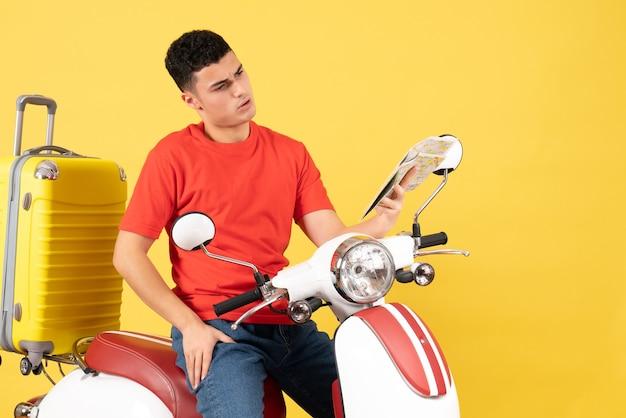 Vue de face jeune homme sur cyclomoteur avec valise en regardant la carte
