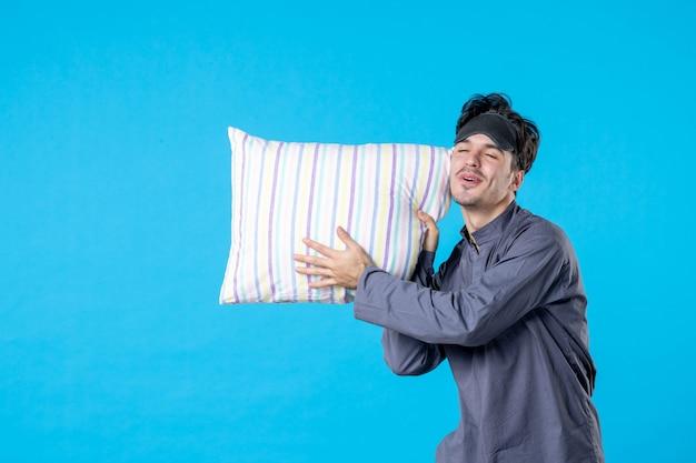 Vue de face jeune homme dans son pyjama tenant un oreiller sur fond bleu cauchemar humain reste rêve nuit réveil tard couleur sommeil