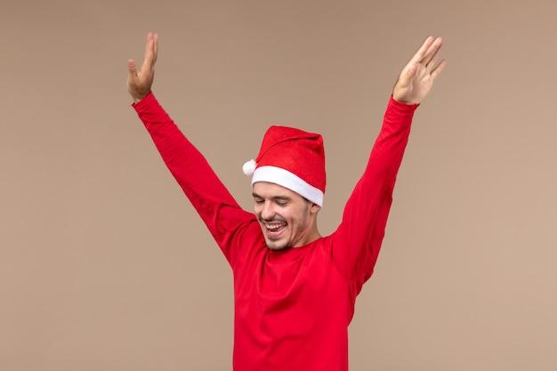 Vue de face jeune homme dansant juste sur fond marron vacances d'émotion de noël