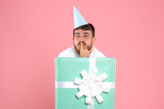 Vue de face jeune homme debout à l'intérieur de la boîte présente sur la photo rose couleur émotion pyjama party de noël