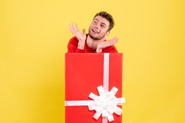 Vue de face jeune homme debout à l'intérieur de la boîte présente