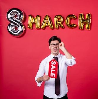 Vue de face jeune homme avec décoration mars holding vente plaque signalétique sur fond rouge couleur femme womans day présent vacances shopping sensuelle
