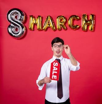 Vue de face jeune homme avec décoration mars holding vente plaque signalétique sur fond rouge couleur femme womans day présent vacances shopping vogue sensuelle