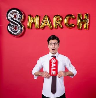 Vue de face jeune homme avec décoration de mars tenant la plaque signalétique de la vente sur fond rouge couleur femme passion womans day vogue sensuel présent vacances