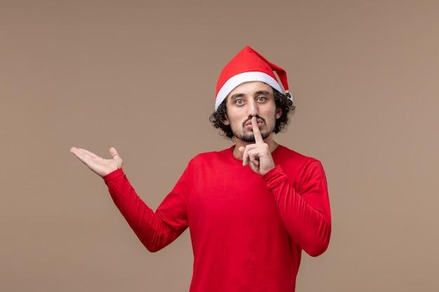 Vue de face jeune homme demandant d'être calme sur fond marron vacances émotion noël