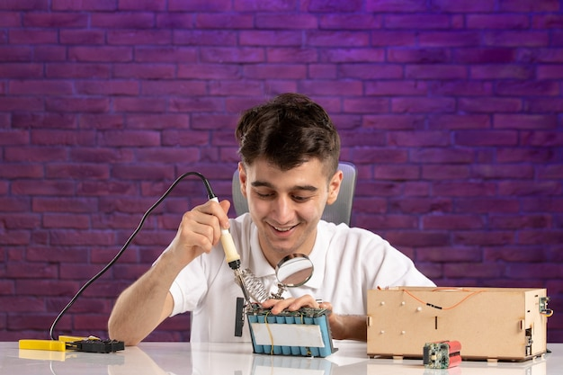 Vue de face jeune homme derrière le bureau essayant de réparer la petite disposition de la maison sur le mur violet