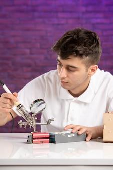 Vue de face jeune homme derrière le bureau essayant de réparer peu de construction sur le mur violet