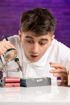 Vue de face jeune homme derrière le bureau essayant de réparer peu de mise en page de la construction sur le mur violet