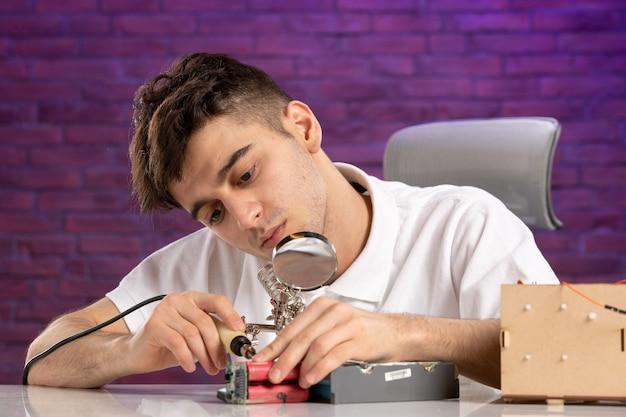 Vue de face jeune homme derrière le bureau essayant de réparer peu de mise en page sur le mur violet