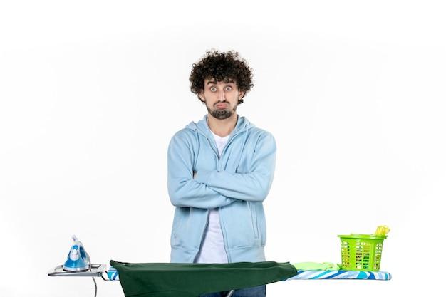 Vue de face jeune homme derrière une planche à repasser sur fond blanc blanchisserie ménage émotion couleur fer à repasser les vêtements de nettoyage