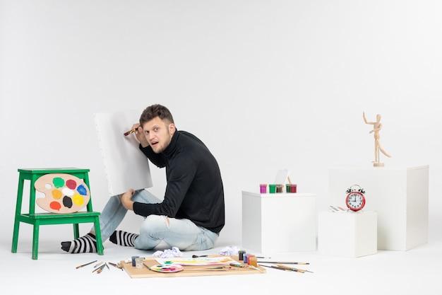 Vue de face jeune homme dessin peinture avec pompon sur un mur blanc couleur image peinture peinture dessin artiste
