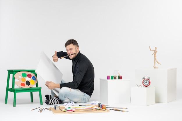 Vue de face jeune homme dessin peinture avec pompon sur un mur blanc couleur travail exposition photo dessin artiste peinture art