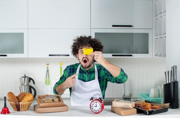 Vue de face d'un jeune homme drôle et émotionnel fou surpris debout derrière la table diverses pâtisseries dessus et montrant une carte bancaire dans la cuisine blanche