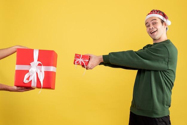 Vue de face jeune homme échangeant des cadeaux avec une main féminine sur jaune
