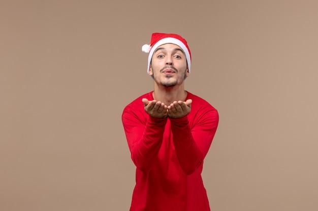 Vue de face jeune homme envoi de bisous d'air sur fond marron vacances de noël émotion mâle