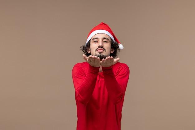 Vue de face jeune homme envoyant des baisers de l'air sur fond marron vacances émotion noël