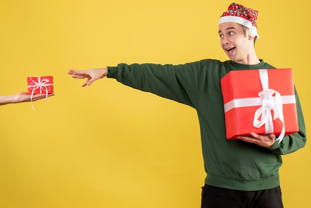 Vue de face jeune homme essayant d'attraper le cadeau dans la main féminine debout sur jaune