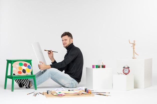 Vue de face jeune homme essayant de dessiner la peinture avec gland sur mur blanc photo artiste peinture art couleurs dessins de peinture