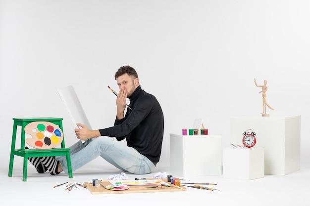 Vue de face jeune homme essayant de dessiner la peinture avec gland sur mur blanc photo peinture art couleur peinture dessin artistes